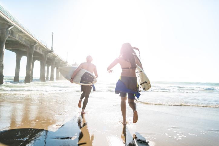 Surfers running on the beach